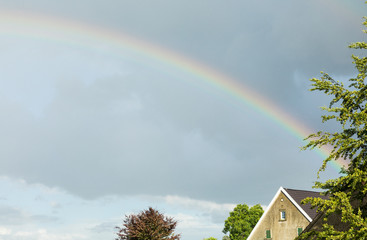 colorful rainbow in the sky with house