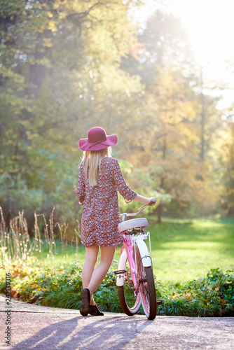 Back view of slim blond fashionable long-haired attractive girl in short dress and pink hat at lady bicycle outdoors on paved summer park alley on beautiful foggy green and golden trees background. - 242139316