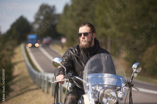 Portrait of handsome bearded biker in black leather jacket and sunglasses sitting on modern motorcycle on roadside on blurred background of twisty road with moving vehicles and green trees.