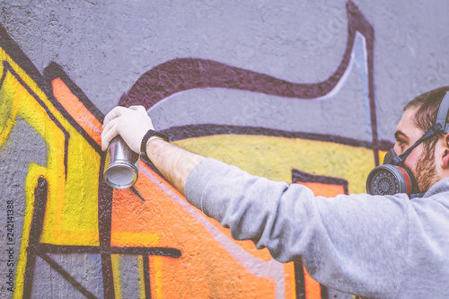 Street artist painting with a color spray can a graffiti on a wall outdoor - Urban man performing with murales - Concept of modern contemporary art - Focus on his hand