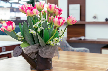 Pink tulips in metal flowerpot on a wooden table.