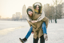 "Постер, картина, фотообои ""Theme New Year Christmas Mood Winter Snow Holidays Valentine Day. Young Caucasian couple lovers joy, laughter fooling water in city park. man holds woman on shoulders as backpack"""
