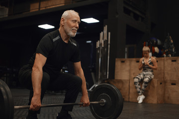 People, age, sports, vitality and powerlifting. Picture of muscular fit mature retired man with strong arms exercising with barbell posing in gym with his young female instructor in background