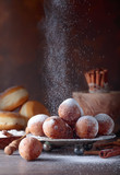 Various donuts powdered with sugar on a brown background.