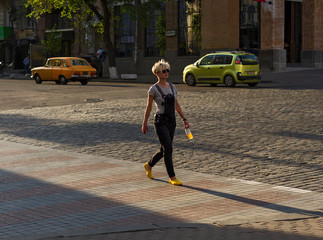 woman crosses the street at a pedestrian crossing