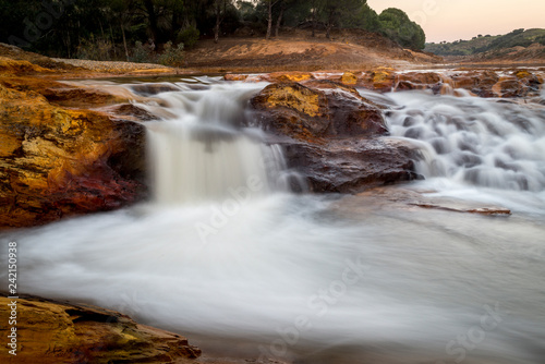 Río tinto en Huelva Andalucía colores rojos y ocres que dan un entorno lunar en un paraje sorprendente cascada agua  - 242150938