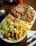 Plato con cuatro trozos de filete de ternera con, ensalada, patatas fritas y champiñones