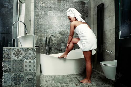Leinwanddruck Bild Woman in towel and bathroom interior