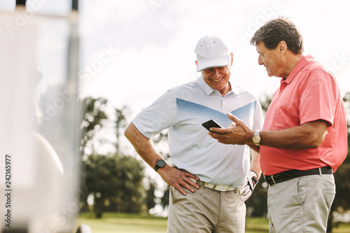 Senior golfers looking the scores on phone after the game
