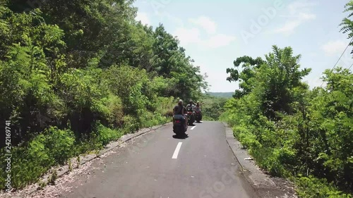Happy tourists riding motor scooter along country road in Nusa Penida, Indonesia. Beautiful view of green trees.