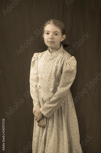 Foto Murales Little girl in early 20th century clothing in replica antique photograph.