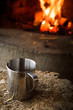 Leinwanddruck Bild - A hot cup of coffee in a metal mug by a camp fire in Pyhä-Hakki National Park, Finland.