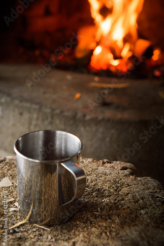 Leinwanddruck Bild A hot cup of coffee in a metal mug by a camp fire in Pyhä-Hakki National Park, Finland.