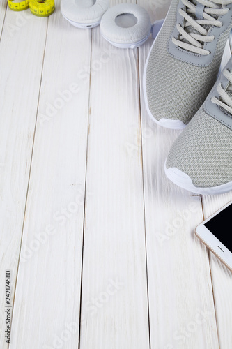 Smartphone, earphones, sport shoes, and measuring tape on wooden board