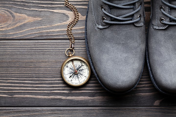 Pair of hiking boots and compass on wooden table