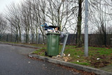 Vollgestopfte Mülltonne an Autobahn-Parkplatz - Stockfoto - 242177119
