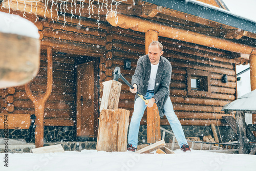 Leinwanddruck Bild Man chopping wood on snowy yard for a house fireplace with heavy snowflakes background . Winter countryside holidays concept image