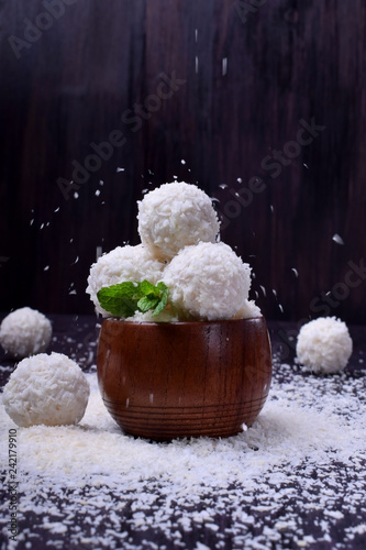 Foto Murales Ball shaped white sweets are sprinkled with coconut flakes against the dark background