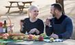 Leinwanddruck Bild - couple having picnic in sunny spring day at countryside