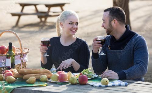 Leinwanddruck Bild couple having picnic in sunny spring day at countryside