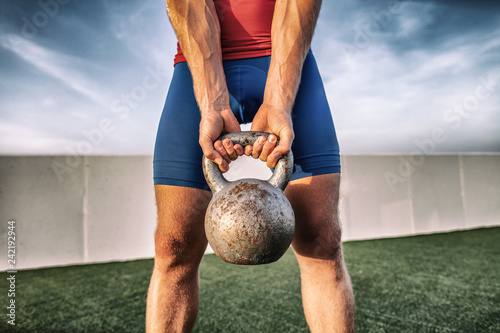 Fitness gym training man lifting heavy kettlebell weight for legs workout. Cross training class in outdoor studio.