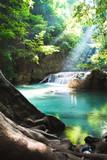 Erawan waterfall, National Park, Kanchanaburi, Thailand. Empty waterfall with sun shining through green foliage.