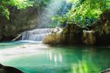 Erawan waterfall, National Park, Kanchanaburi, Thailand. Empty waterfall with sun rays shining through green foliage.