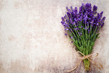 Fototapeta Lawenda - Lavender flowers, bouquet on rustic background, overhead. © gitusik