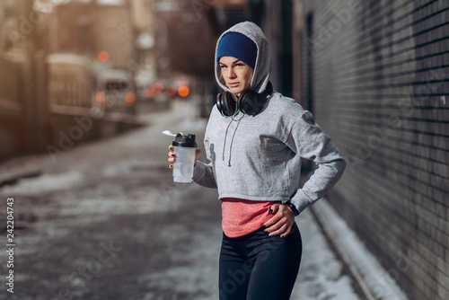Fit woman drinking protein shake on winter day in city. Sporty woman in headphones