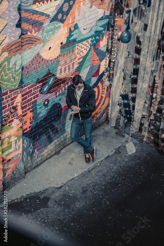 Man and woman on the street at a colorful wall. Retro style. Street Photography - 242213770