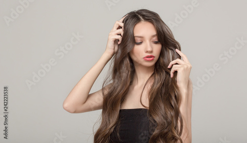 Fashion woman, hair confusion. Long wavy hair and makeup