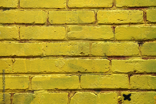 Yellow colored peint brick wall - 242231541