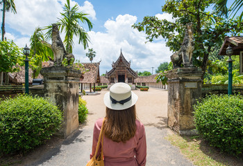 Back view of female tourist looking to the beautiful architecture of Wat Inthrawat temple is one of the finest examples of classic Lanna style architecture in Northern Thailand.