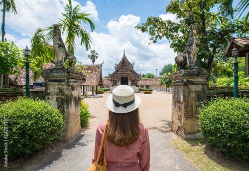 Leinwandbild Motiv Back view of female tourist looking to the beautiful architecture of Wat Inthrawat temple is one of the finest examples of classic Lanna style architecture in Northern Thailand.