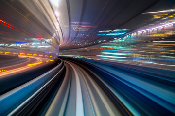 Motion blur of a city and tunnel from inside a moving monorail in Tokyo
