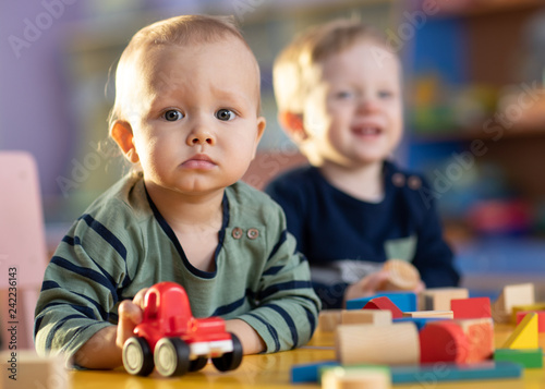 Leinwandbild Motiv Baby boys with toy car and building blocks in kindergarten