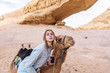 Young woman smiling posing with a camel in the middle of the jordan desert
