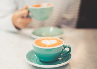 a cup of hot latte coffee with heart shape latte art, coffee lover concept, autumn color tone