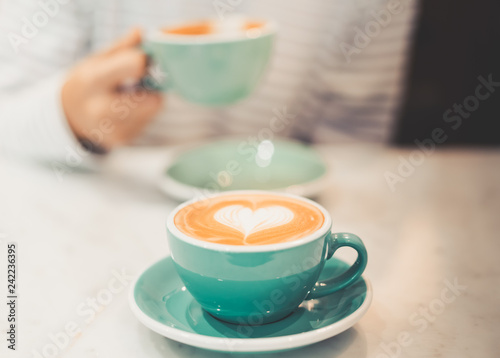 Leinwanddruck Bild a cup of hot latte coffee with heart shape latte art, coffee lover concept, autumn color tone