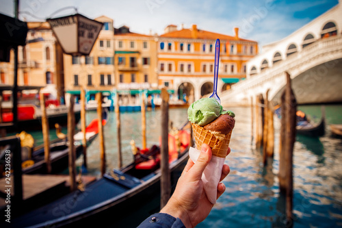 Hand man holds an Italian ice cream on background of Grand Canal and Handol in Venice, Italy. tourism. - 242236538