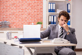 Young businessman working in the office - 242238340