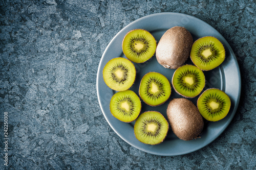 Top view of kiwi fruit in a plate with copy space on stone background made of marble