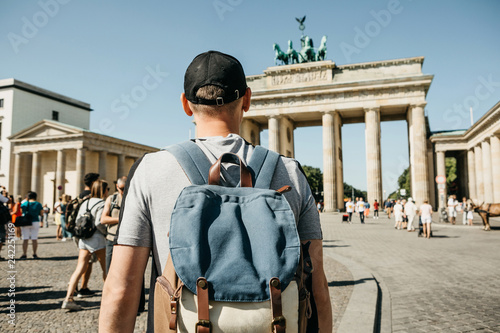 A tourist or a student with a backpack in Berlin in Germany visits the sights. Ahead is the Brandenburg Gate and unrecognizable blurred people.