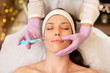 Leinwandbild Motiv people, beauty, cosmetology and technology concept - beautician with syringe doing hyaluronic acid injection for lip augmentation to young woman