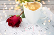 valentines day and holidays concept - close up of calendar sheet with 14th february date marked by heart shape, coffee cup and red rose