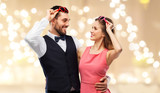 valentines day, love and people concept - happy couple in heart-shaped sunglasses over beige background with festive lights - 242253123