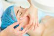 Leinwandbild Motiv Cosmetologist makes facial massage to a young woman.
