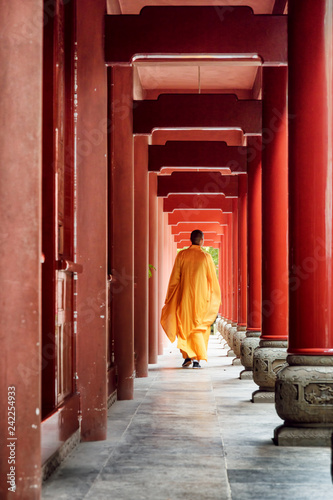 Chinese Buddhist monk walking along red wooden corridor