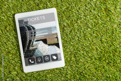 top view of digital tablet with tickets app on screen on green grass, energy efficiency concept