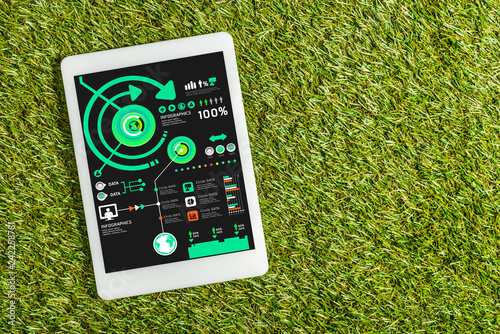 top view of digital tablet with charts on screen on green grass, energy efficiency concept